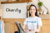 junge asiatische freiwillige Mädchen auspacken Karton mit Kleidung