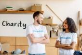 Fotografie zwei fröhliche multikulturelle Freiwillige stehen mit gekreuzten Armen, lächeln und schauen einander an