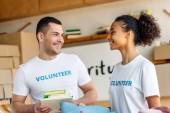 zwei fröhliche multikulturelle Freiwillige im Gespräch, während sie Bücher und Kleidung halten