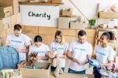 Fotografie Gruppe junger multikultureller Freiwilliger packt Pappkartons mit Kleidung, Büchern und Spielzeug aus