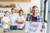 Fotografia selective focus of handsome man holding placard with thank you text while standing near multicultural volunteers in charity center