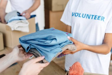 cropped view of volunteer giving clothes to woman in charity center