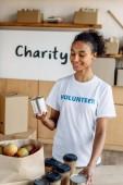 Fotografie hübsche afrikanische amerikanische Freiwillige halten Zinn, während sie in der Nähe von Tisch mit Einwegbechern und Papiertüte mit Äpfeln stehen