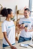 Fotografie fröhliche multikulturelle Freiwillige lächeln und reden, während sie Papierbecher halten