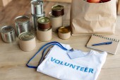 Fotografia white t-shirt with volunteer inscription, badge,  tins, paper bag and notebook on wooden table