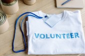 Fotografia white t-shirt with blue volunteer inscription, badge and tins on wooden table