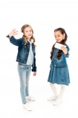 full length view of kids in denim clothes taking selfie on white