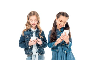 two kids in denim clothes using smartphones isolated on white