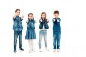 Ganzkörperansicht von vier Kindern in Jeanskleidung, die die Daumen nach oben zeigen, isoliert auf Weiß