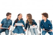 Fotografia four smiling kids in denim clothes sitting on chairs and using digital tablets isolated on white