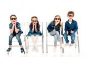 čtyři užaslí děti ve 3D brýlích sedícího na židlích na bílém