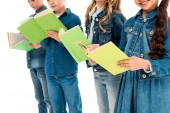 partial view of four children in denim clothes reading books isolated on white