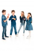 full length view of children in denim clothes eating apples on white