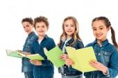 Fotografie čtyři děti v džíně oděvy držící knihy izolované na bílém