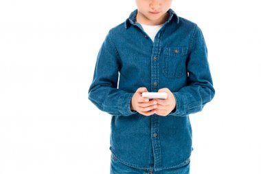 Partial view of kid in denim shirt using smartphone isolated on white stock vector