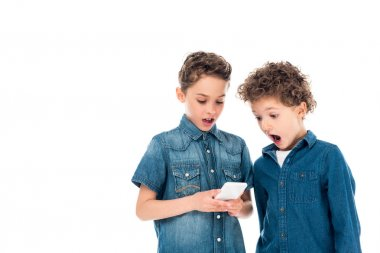 two shocked kids using smartphone isolated on white