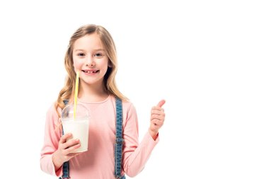 Smiling kid holding milkshake and showing thumb up isolated on white stock vector
