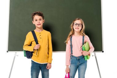two schoolchildren with backpacks and books standing near blackboard isolated on white