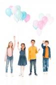 Ganzkörperansicht von vier Kindern mit Luftballons auf weißem Grund