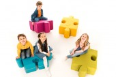 overhead view of kids sitting on jigsaw puzzles on white