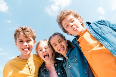 low angle view of four kids showing tongues under sky