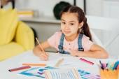 szelektív középpontjában a boldog gyermek nézi a kamerát, miközben színes ceruza közelében papír otthon
