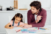Fotografie handsome father pointing with finger at paper near cute daughter