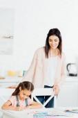 Fényképek boldog barna anya nézett aranyos lánya rajzot otthon