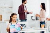 selective focus of cute kid holding paper with colorful stripes while standing near parents at home