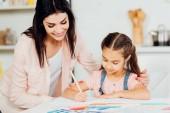 Fényképek boldog anya nézett aranyos lánya rajzot papíron otthon