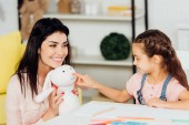 Photo cute daughter pointing with finger at soft toy near happy mother