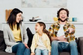 Photo happy father laughing while watching tv near attractive wife and kid