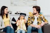 Veselý chlapec gestikulovat při nošení náhlavní soupravy ve virtuální realitě poblíž šťastných rodičů doma