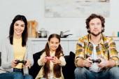 roztomilá a šťastná holka, která hraje doma videohru s rodiči