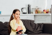 Photo cheerful kid holding remote controller while eating tasty popcorn