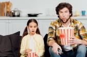 Fényképek meglepett, apa és lánya néz film és gazdaság vödör Popcorn otthon