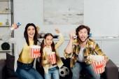 Fotografie glückliche Familie beobachtet Meisterschaft und gestikulieren beim Jubeln zu Hause