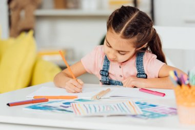 Selective focus of cute kid drawing on paper at home stock vector
