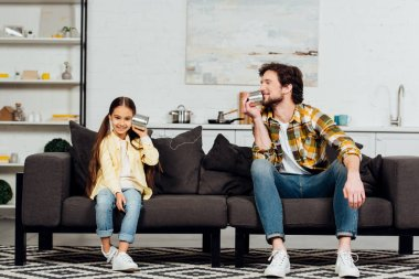 happy daughter holding can phone and cheerful father talking and sitting on sofa