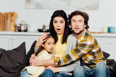 shocked husband and wife watching tv and hugging cute daughter