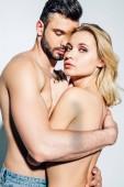 nečistý muž objímat nahou blondýnu ženu, která hledí na kameru na bílou