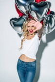 Fotografie selective focus of cheerful blonde girl holding heart-shape balloons and gesturing on white