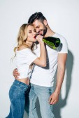 cheerful blonde girl drinking champagne from bottle near handsome man on white