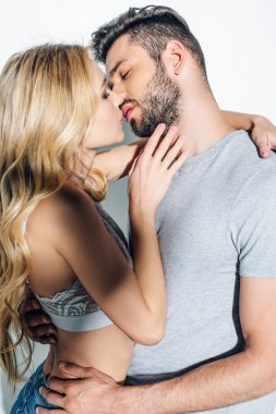 attractive blonde woman kissing with handsome man on white