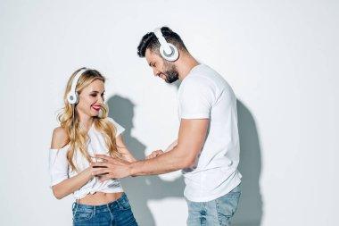 happy man in headphones touching cheerful blonde girl on white
