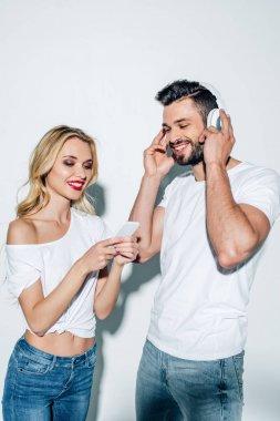 cheerful girl holding smartphone near bearded man in headphones on white