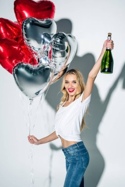 happy blonde girl holding bottle of champagne and heart-shape balloons on white