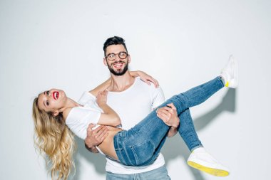 happy man in glasses holding in arms attractive blonde girl on white