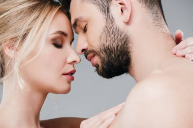 close up of attractive woman hugging man with closed eyes on grey