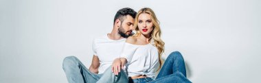 panoramic shot of handsome bearded man sitting and looking at attractive blonde girl on white